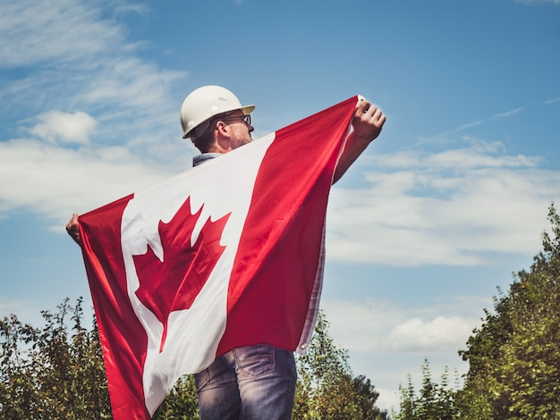 Young engineer, white hardhat and canadian flag in the park against the backdrop of green trees and the setting sun, looking into the distance. close-up. concept of labor and employment