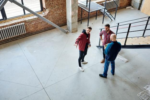 Молодой инженер с бокалом кофе, объясняя свою точку зрения на незавершенное строительство коллегам на рабочем совещании