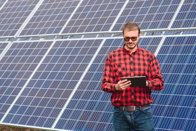 Молодой инженер с планшетным компьютером, стоящим возле солнечных батарей на открытом воздухе