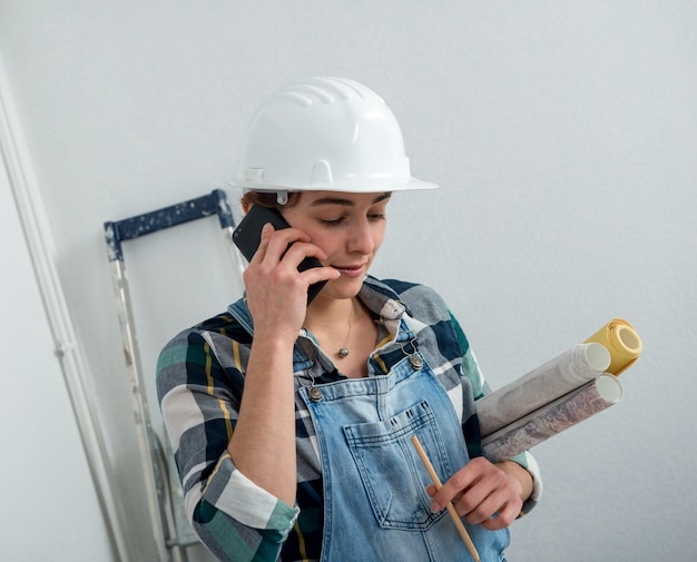 Young engineer woman with safety helmet talking on phone