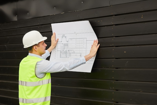 Young engineer in work helmet and reflective clothing examining the blueprint while standing outdoors