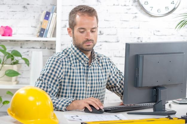그의 컴퓨터에서 작업하는 젊은 엔지니어