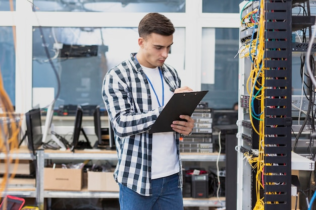Young engineer working in server room