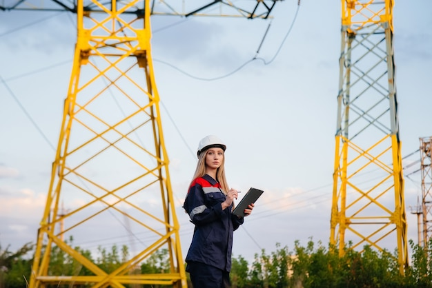 A young engineering worker inspects and controls the equipment of the power line. energy.