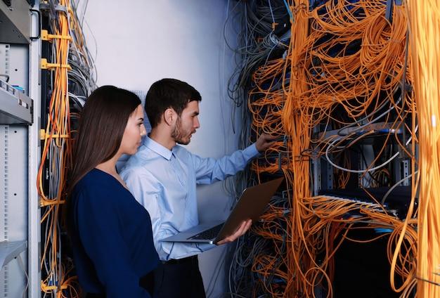 Молодые инженеры, соединяющие кабели в серверной