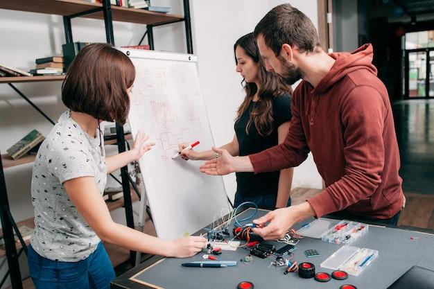 研究室で電子スキームについて話し合う若いエンジニア。