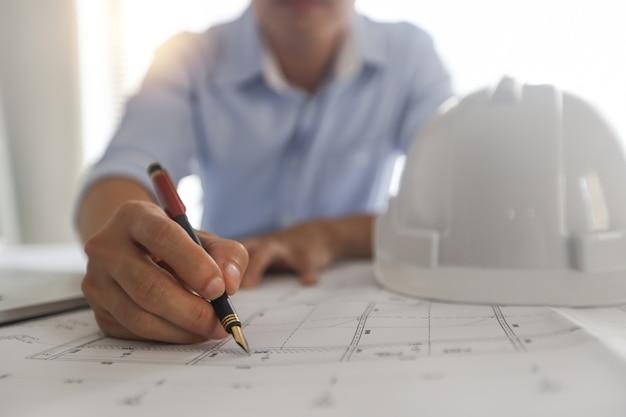 Молодые инженеры или архитектор, держащий ручку и план чертежа на светокопии на рабочем месте.
