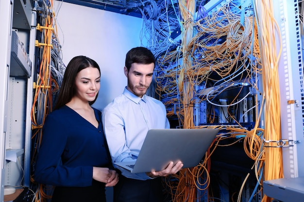 Молодые инженеры с ноутбуком в серверной комнате