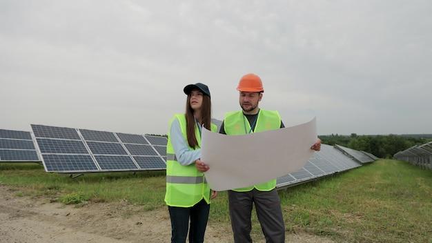 젊은 엔지니어 작업자가 태양열 계획을 손에 들고 태양열 패널 스테이션에 서 있습니다