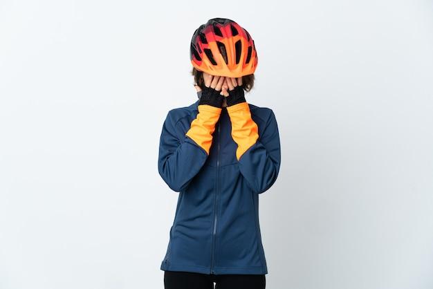Молодая английская велосипедистка изолирована на белой стене с усталым и больным выражением лица