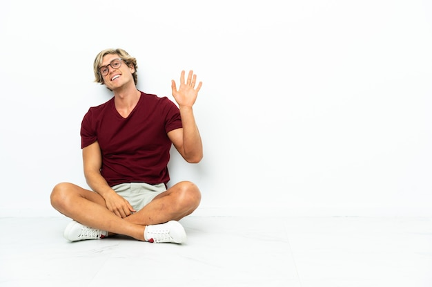Young english man sitting on the floor saluting with hand with happy expression