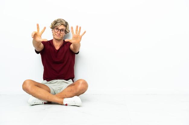 指で8を数える床に座っている若いイギリス人男性