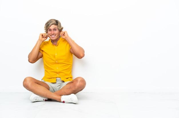 欲求不満で耳を覆っている床に座っている若いイギリス人男性