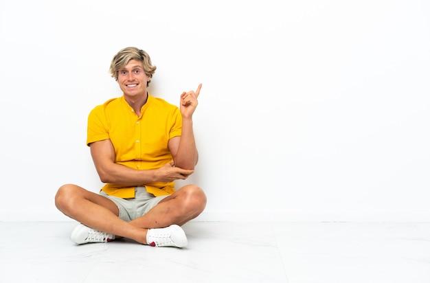 행복하고 가리키는 바닥에 앉아 젊은 영어 남자