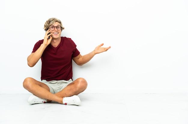 누군가와 휴대 전화로 대화를 유지하는 바닥에 앉아 젊은 영어 남자