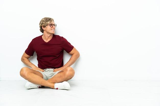 腰に腕を組んでポーズをとって笑顔で床に座っている若いイギリス人男性