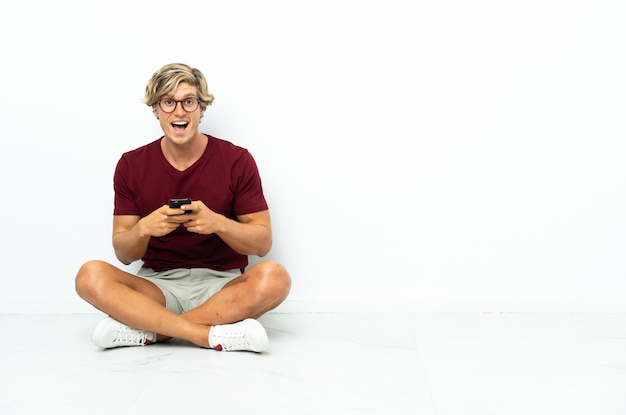 놀란 바닥에 앉아 메시지를 보내는 젊은 영어 남자
