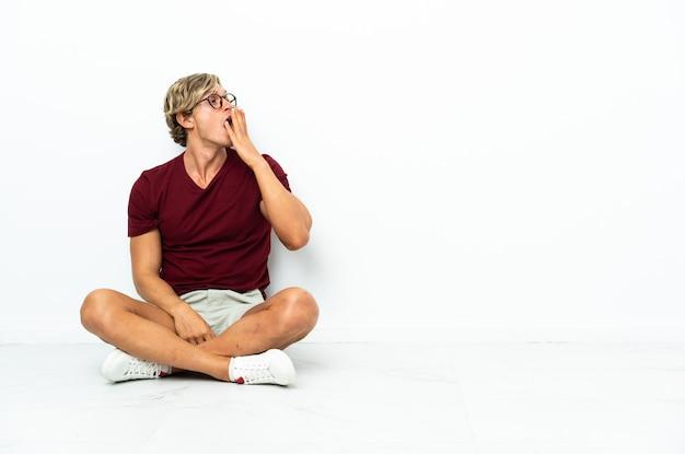 あくびをし、手で大きく開いた口を覆って床に座っている若いイギリス人男性