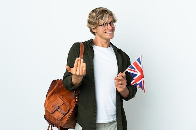 Молодая англичанка, держащая флаг соединенного королевства, приглашающая прийти с рукой. счастлив что ты пришел