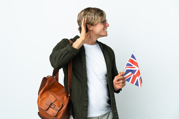 귀에 손을 넣어 뭔가를 듣고 영국 국기를 들고 젊은 영어 여자