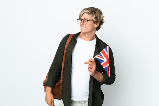 Молодая англичанка, держащая флаг соединенного королевства, смотрит в сторону и улыбается