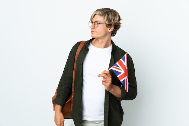 Молодая англичанка, держащая флаг соединенного королевства, глядя в сторону