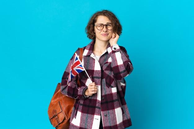 Молодая англичанка, держащая флаг соединенного королевства на синем фоне, разочарована и закрывает уши
