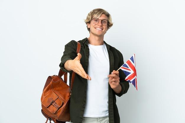 좋은 거래를 닫기 위해 악수하는 영국 국기를 들고 젊은 영어 여자