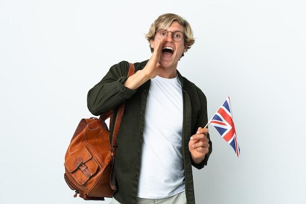 Молодая англичанка, держащая флаг соединенного королевства, кричит с широко открытым ртом