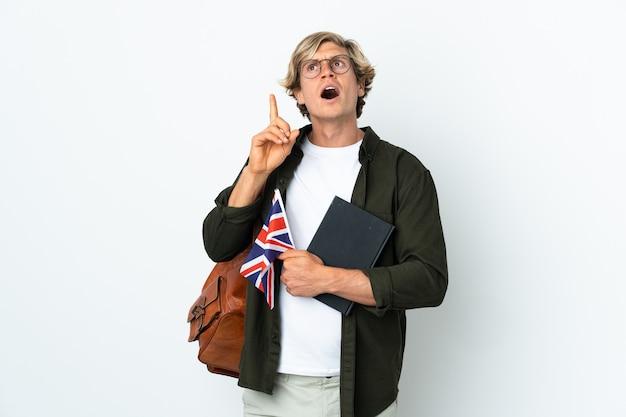 Молодая англичанка, держащая флаг соединенного королевства, думает о идее, указывая пальцем вверх