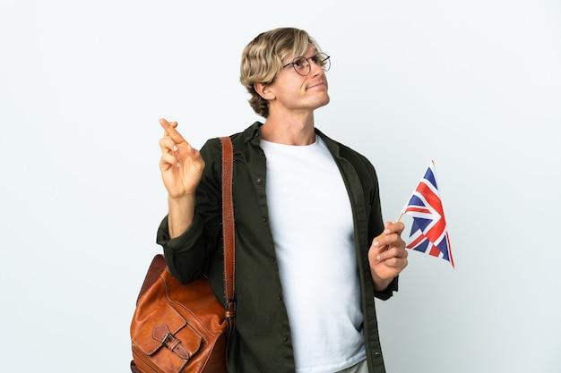 Молодая англичанка держит флаг соединенного королевства со скрещенными пальцами и желает всего наилучшего
