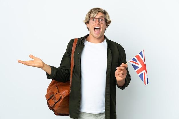 Молодая англичанка с шокированным выражением лица держит флаг соединенного королевства