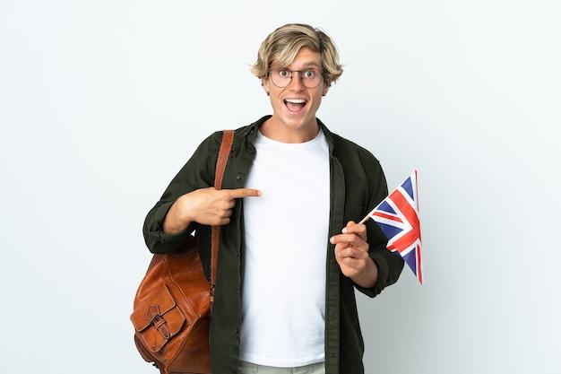 Молодая англичанка с удивленным выражением лица держит флаг соединенного королевства
