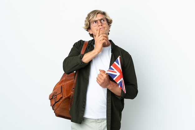 Young english woman holding an united kingdom flag having doubts while looking up