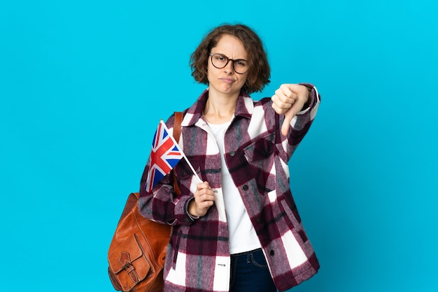 Young english woman holding an united kingdom flag isolated on blue background showing thumb down with negative expression