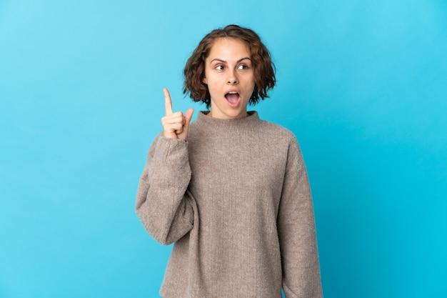 指を上に向けるアイデアを考えて青い壁に孤立した若いイギリス人女性