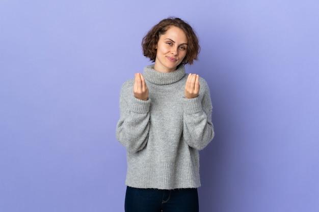 Молодая англичанка изолирована на фиолетовой стене делает денежный жест, но разрушена