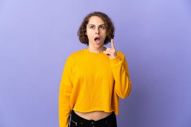 指を上に向けるアイデアを考えて紫色の壁に孤立した若いイギリス人女性