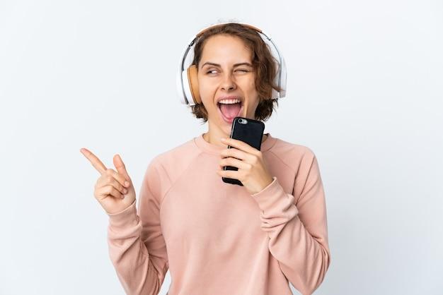 Молодая англичанка изолирована на белой стене, слушает музыку с помощью мобильного телефона и поет