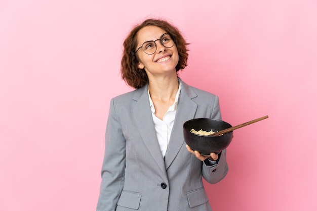Young english woman isolated on pink wall looking up while smiling while holding a bowl of noodles with chopsticks