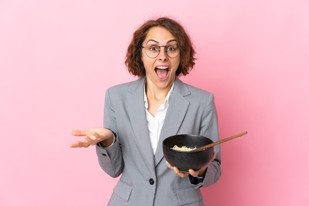 Young english woman isolated on pink wall with shocked facial expression while holding a bowl of noodles with chopsticks