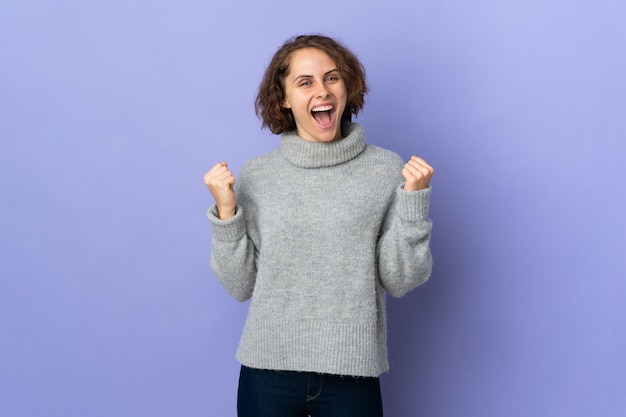 Young english woman isolated on purple background celebrating a victory in winner position