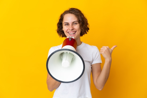 Young english woman isolated on yellow wall shouting through a megaphone and pointing side