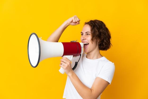 Молодая англичанка на желтом кричит в мегафон, чтобы объявить что-то в боковом положении