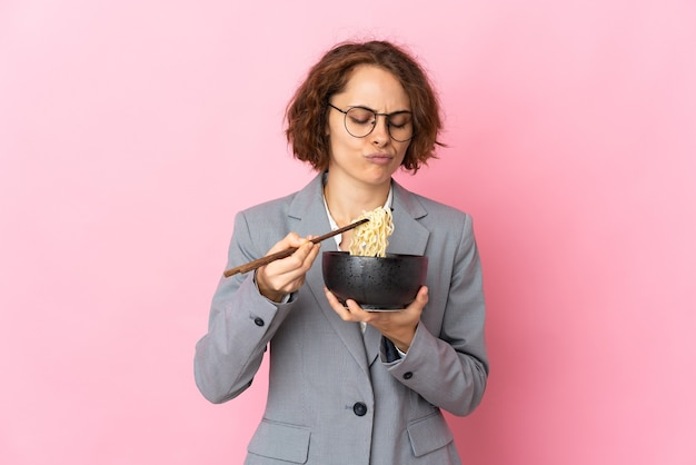 Young english woman on pink holding a bowl of noodles with chopsticks