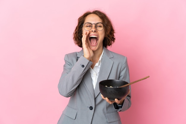 Young english woman on pink shouting with mouth wide open while holding a bowl of noodles with chopsticks