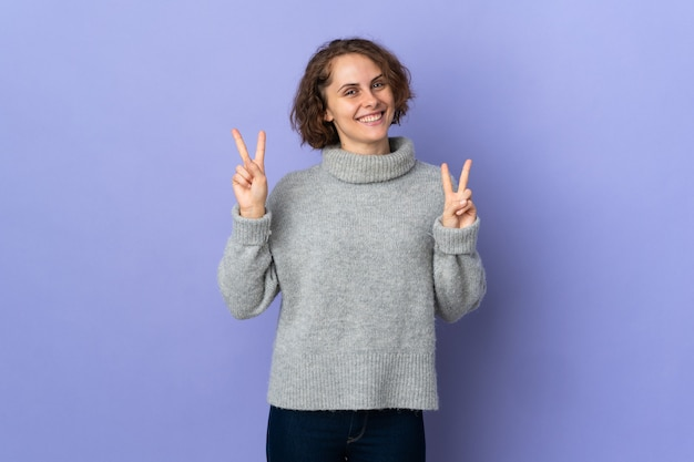 Young english woman on purple background showing victory sign with both hands