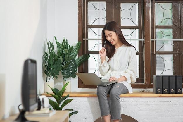 노트북을 사용하여 인터넷으로 홈 오피스에서 일하는 젊은 기업가 아시아 비즈니스 여성
