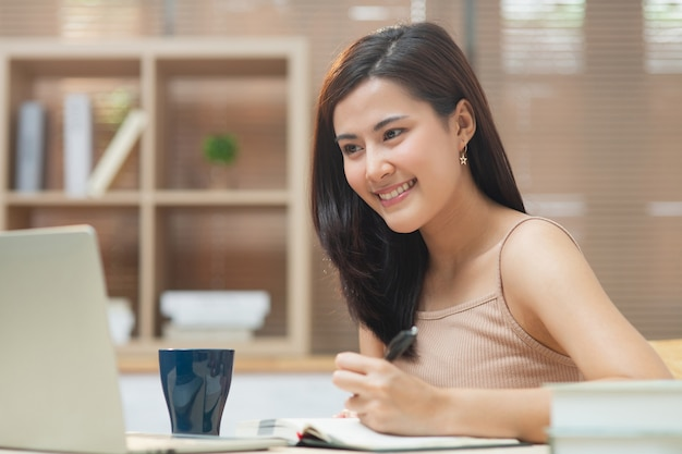 Young entrepreneur asian business woman working at home office with internet using computer