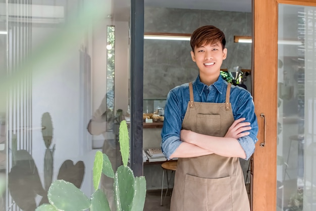 Young entrepreneur asian man at front door of his own cafe